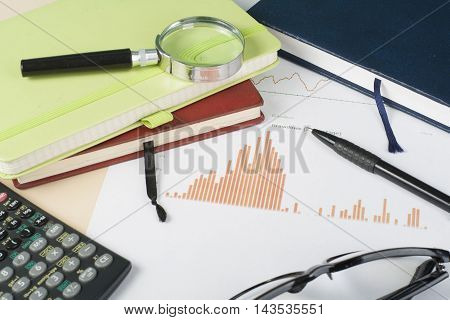 Home savings, budget concept. Chart, notepad, pen, calculator and coins on wooden office desk table