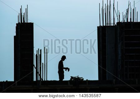 Silhouette of construction worker setting up fittings for concrete building