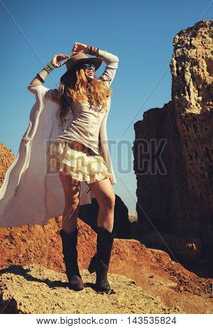 Outdoor fashion photo of young happy woman in hat, sitting on a fur against rocks, hands up, safari travel concept