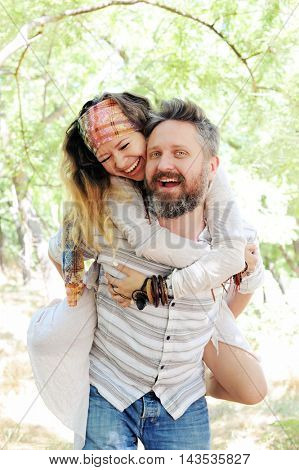 Boho style beautiful joyful couple, indie style, hipster outfit, bohemian outfit, woman embracing man, in love, sunny outdoor in park