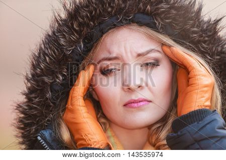 Portrait of pretty fashionable woman suffering from headache pain. Young girl in jacket with hood caught cold flu virus. Autumn fall winter fashion.