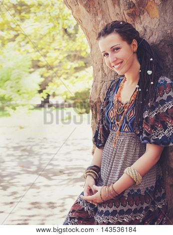 Cute smiling hippie indie style woman with dreadlocks,  dressed in boho style ornamental dress posing outdoor, empty space for text