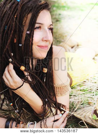 Calm smiling girl portrait with dreadlocks, resting on the dry grass in park, have a beads in her hair
