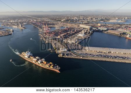 Long Beach, California, USA - August 16, 2016:  Afternoon aerial view of busy container cargo facilities and passing ship.