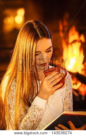 Woman drinking cup of coffee reading book at fireplace. Young girl with hot beverage relaxing heating warming up. Winter at home.