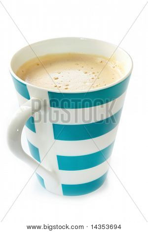 Blue and white striped mug of frothy coffee.  Isolated on white.