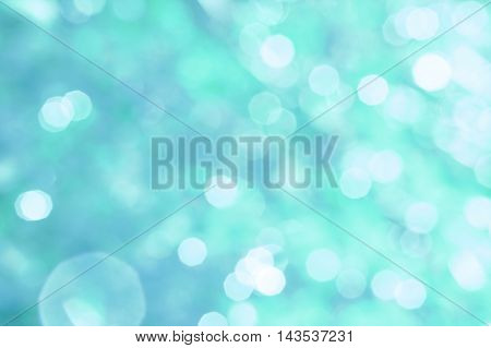 Abstract turquoise background with white bokeh and patches of light