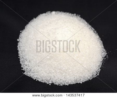 granulated sugar on a black background isolated