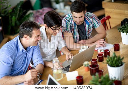 Three business people working on laptop shop in coffee