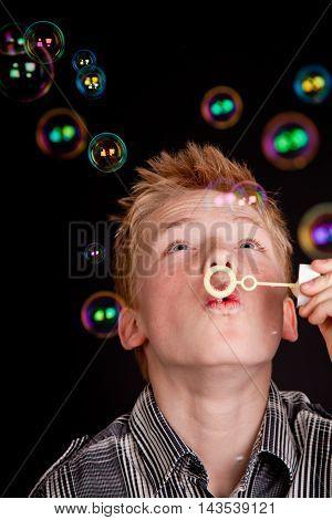 Teenage Boy Having Fun Blowing Soap Bubbles