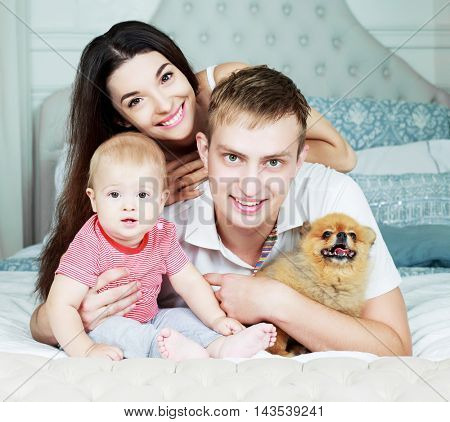 happy family with a baby and a dog  in bed at home