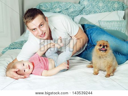 happy young father with a baby and a dog  in bed at home
