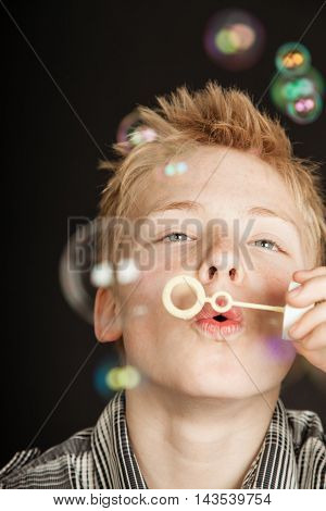 Boy Blowing Bubbles Through Plastic Wand
