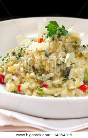 Risotto in a white bowl, garnished with shaved Parmesan cheese and parsley.  This is a chicken risotto.