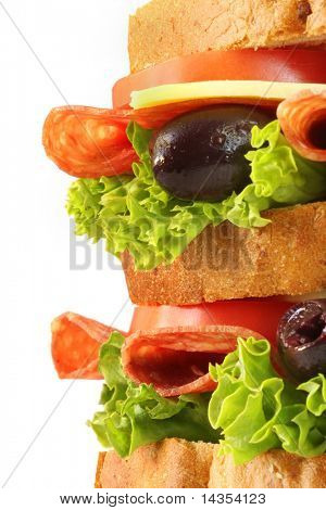 Salami sandwich, with black olives, curly lettuce, tomatoes and cheese.  Triple-decker, in close-up.