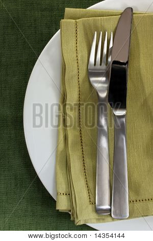 Place setting ~ knife, fork and plate with green linen.