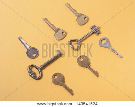 Set od assorted different keys on wooden background.