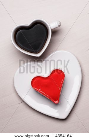Heart shaped coffee cup and jelly cake on wooden kitchen table.