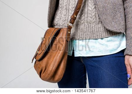 Closeup of attractive young woman wearing jeans and leather brown handbag on white background