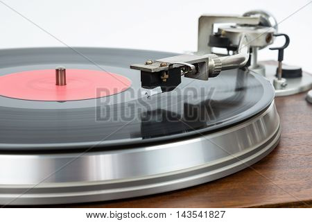 Closeup of turntable with vinyl record on white background