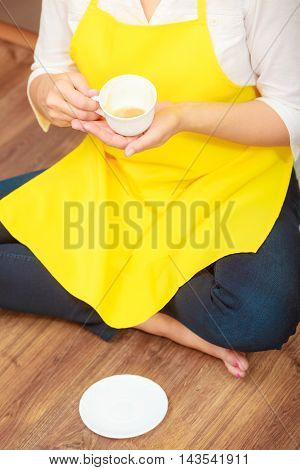Woman in apron holding cup of coffee in kitchen. Housewife female relaxing resting sitting on floor.