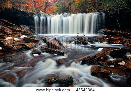 Autumn waterfalls in park with colorful foliage.