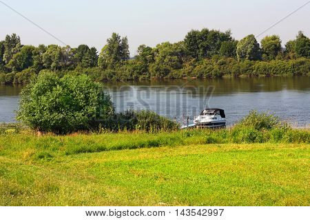 Rural landscape with the view of small motorboat on the riverside
