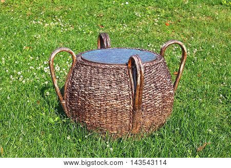Decorative wooden wicker side table with four handles on grass