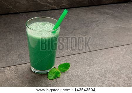 Fresh spinach and mint smoothie with green straw on black background