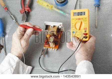 Hand of electrician with multimeter probe at  electrical switchgear cabinet. Engineering tools.
