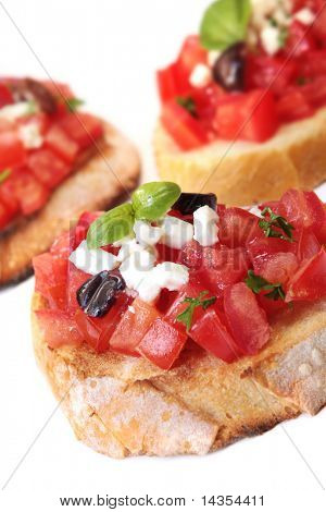 Bruschetta - crujiente pan tostado con tomate, aceitunas negras, queso de cabra y albahaca.