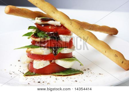 Caprese salad in a stack, with bread sicks.  Tomato and basil salad, with baby mozzarella and balsamic.