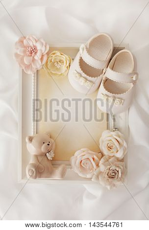 empty photo frame and baby shoes