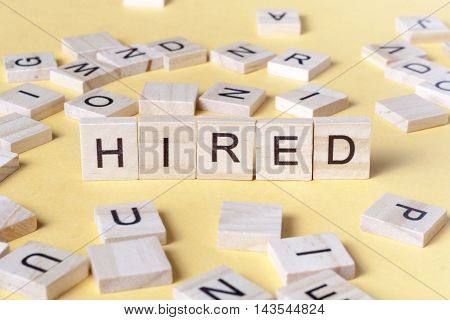 text of HIRED on cubes. Wooden abc.