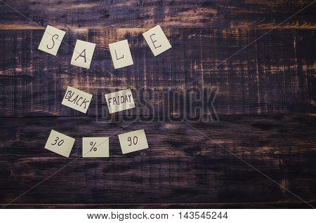 sale written on leaflets on a wooden black background