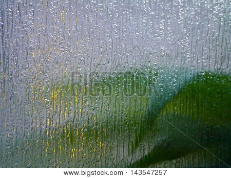 Blurred background with green leaves viewed through multicolored textured and translucent glass.
