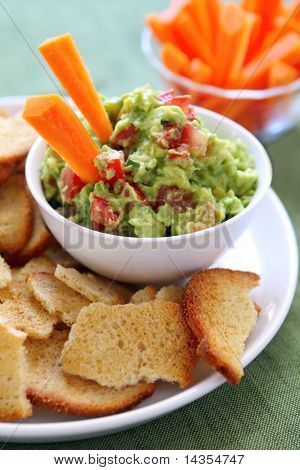 Avocado guacamole served with carrot sticks and bagel crisps - a healthy variation of this delicious snack.