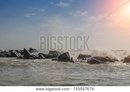 sea waves hit about rocks into summertime