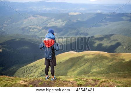 Man in sportswear stands on the mountain and holds his son on the shoulders on the background of the mountains and the cloudy sky. Boy wears multi-colored big size windcheater. Outdoors. Horizontal.