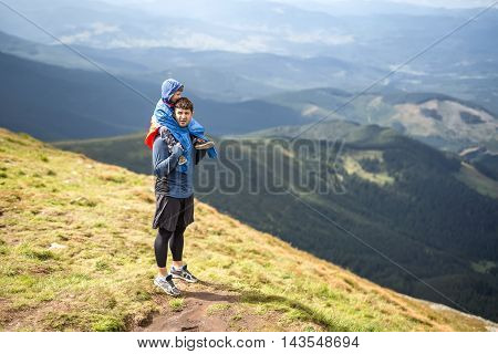 Father in sportswear stands on the mountain and holds his son on the shoulders on the background of the mountains and the cloudy sky. Boy wears multi-colored big size windcheater. Horizontal.
