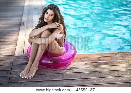 Charming girl in a white swimsuit sits on the pink rubber ring and looks to the side with parted lips on the background of the swimming pool. She hugs her legs with her hands. Horizontal.