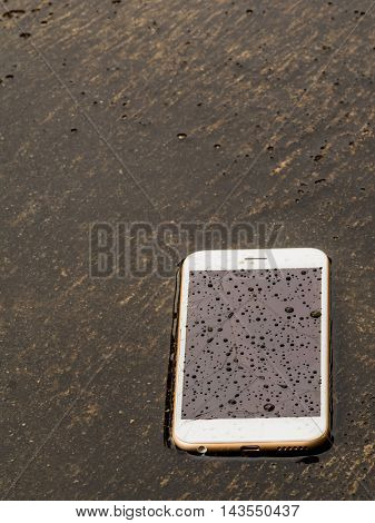 Damage and wet smart phone dropped on flooding floor with water drop on screen after the rain Copy space