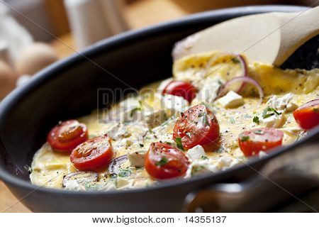 Cooking omelet in a pan, ready to serve.  With Cherry tomatoes, red onion, goat's cheese and parsley.  Shallow DOF.