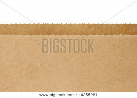 Top serrated edges of an open brown paper bag, over white background.