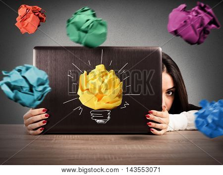 Businesswoman is protected behind the computer screen from paper balls