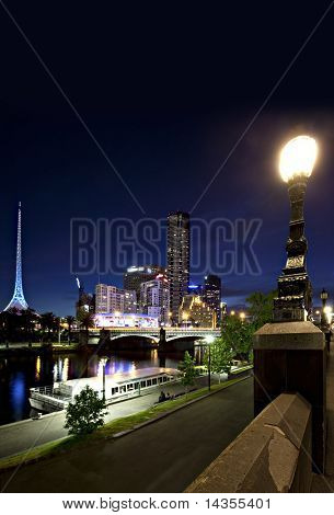 Melbourne, Australia by night.  View over Yarra River with Arts Centre spire, Princes Bridge and Southgate, with river barges.