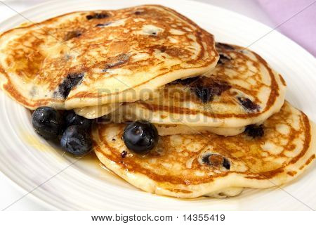 Buttermilk pancakes with blueberries and maple syrup.  A sweet treat.