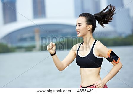 young and beautiful asian female runner running by a lake in city park.