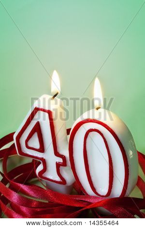 Number 40 candles, surrounded by red ribbon.  40th birthday or anniversary.