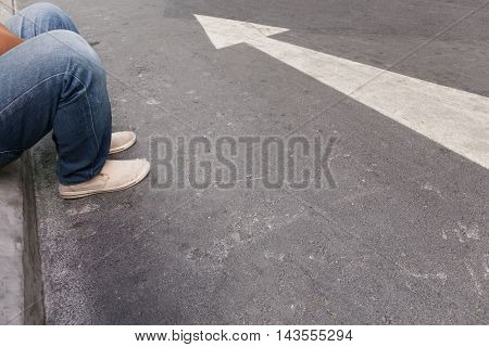 The person sitting next to the arrows on the street.
